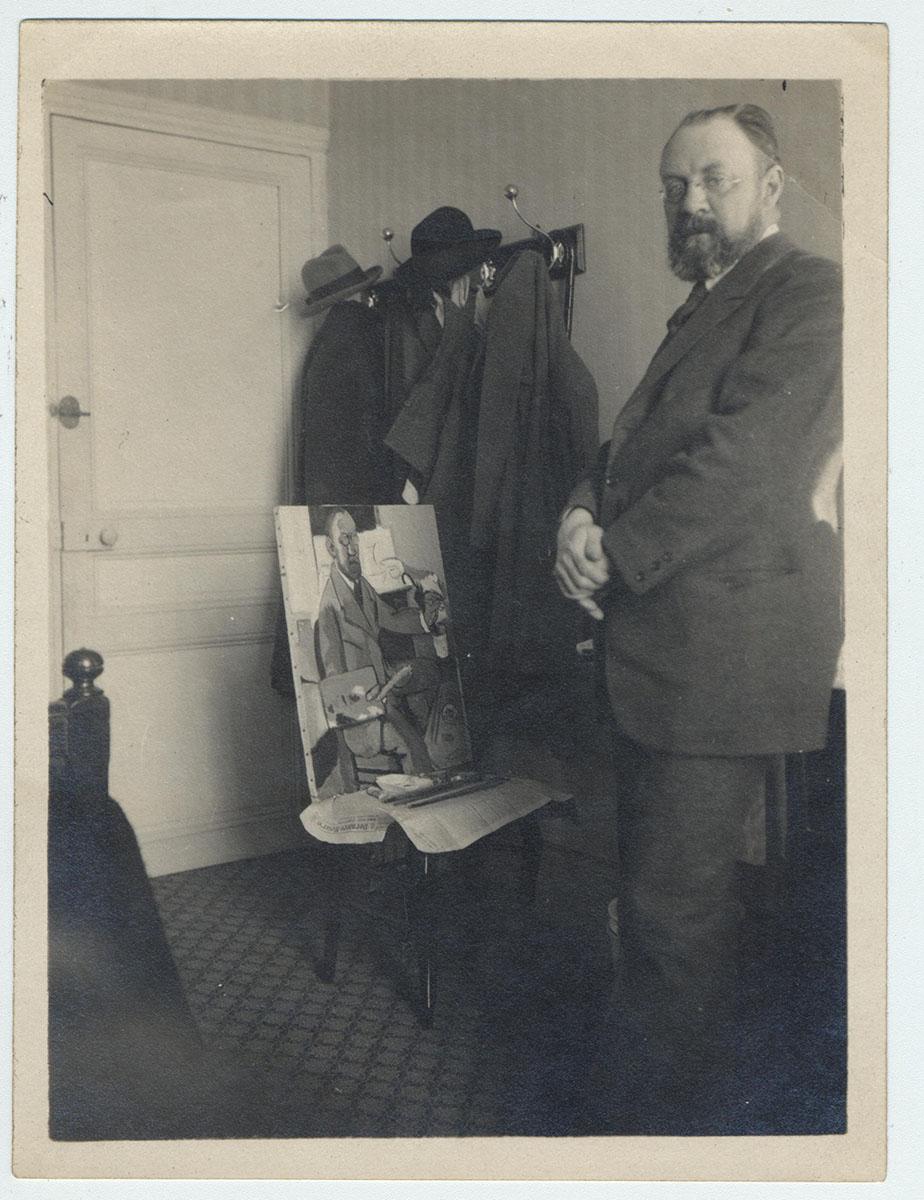 Photographie : Henri Matisse posant devant son autoportrait, hôtel Beau Rivage, Nice, 1918
