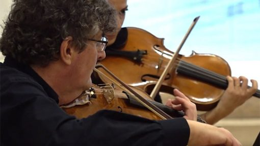 Gros plan sur deux violonistes en train de jouer